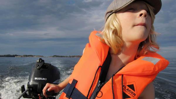 Kind fährt Motorboot, Stockholm Schärengarten Schweden