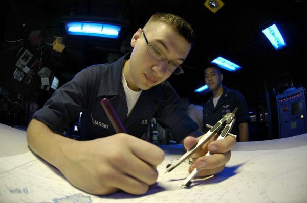 Ein Kadett der US-Navy trägt eine Koppelposition auf der Seekarte ein